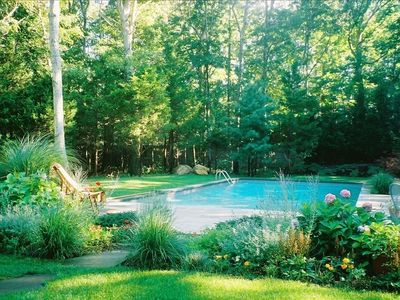 Long view of beautiful sunny pool and garden area