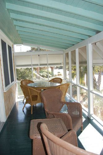 Screened in porch with table and chairs off den