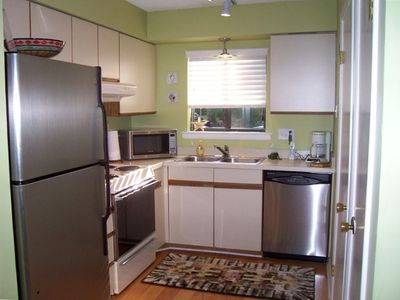 A full sunny kitchen with updated appliances, washer, and dryer, and pantry.
