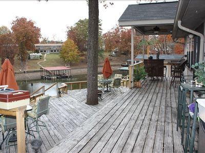 Triple tier deck overlooking boat dock and lake cove.