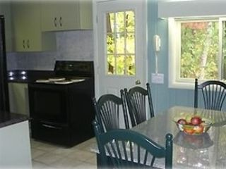 Full kitchen with granite counter tops and table.