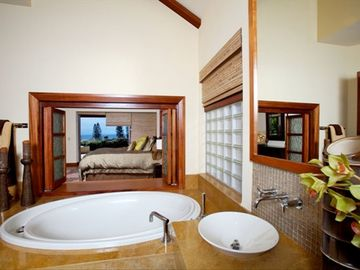 Jetted bathtub & vessel sinks in Master Bathroom; bifold doors open to Bedroom