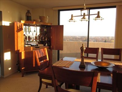 Elegant dining with hardwood table for 8, full-lighted bar, and stunning views