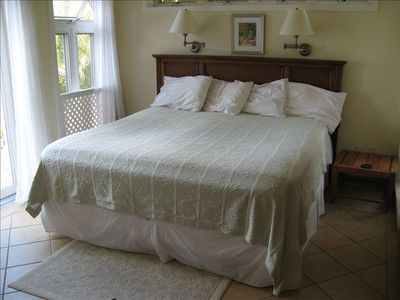 King bed with view of Caribbean and door onto veranda - has en suite bath and AC