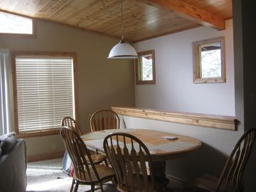 Dining area, stairway down, picture windows, vaulted ceiling