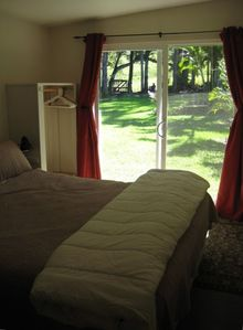 Bedroom opens to a groomed acre of lawn with views of Haleakala