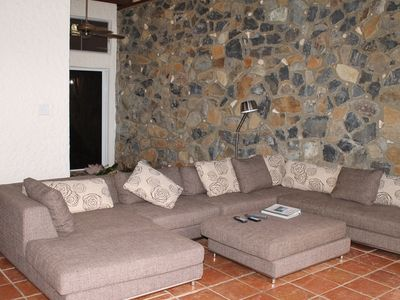 Comfortable living area with plenty of seating - native stone wall highlights.