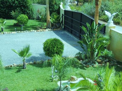 Inside Gated Grounds with various areas of Lawns, Palm Trees & Tropical Plants