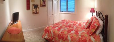 Panoramic photo of bedroom w/ queen bed, flat screen TV, & ceiling fan w/ remote