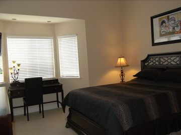 Master bedroom bay window with office desk, dresser, flat panel TV.