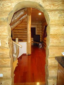A log arch to travel thru to the kitchen.