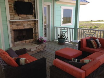 Second outdoor seating area with fireplace and flat screen TV