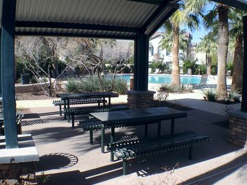 Shaded picnic tables with few a pool.