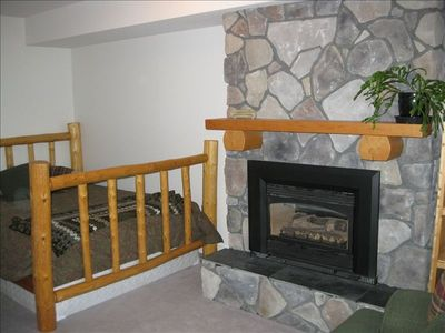 A Welcoming Log Bed and Cozy Fireplace Offer an Escape from the Rat-Race.