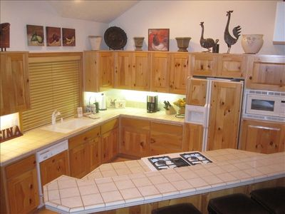 Kitchen with knotty pine cabinetry, gas cooktop, lots of cookware & essentials.