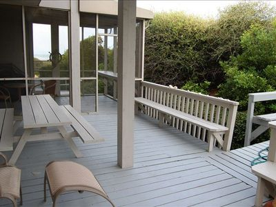View of the lower deck with picnic table and screened in porch ...