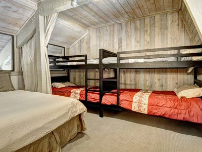Loft with queen bed and two twin bunkbeds with privacy curtain for the kids.