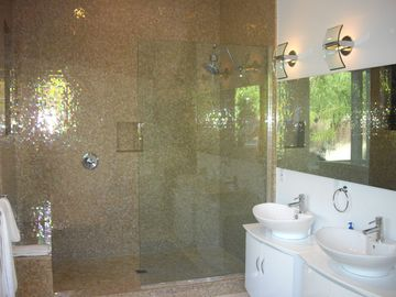 Huge walk in shower in master with iridescent tile and dual vanities.