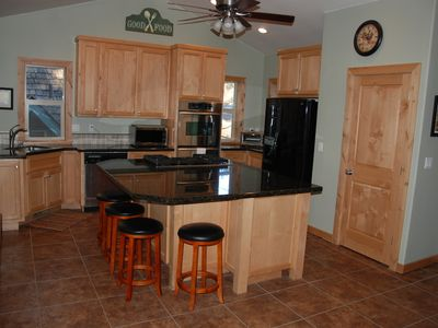 Fully equipped gourmet kitchen with 5 burner gas range and seating for 5 at bar