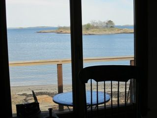 Sweet view inside house to deck, looking through railings to island in winter.
