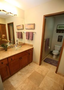 Travertine flooring. Pocket door separates the shower, bathtub and toilet area.