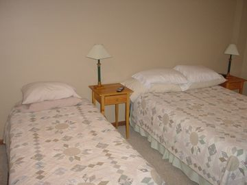 Bedroom in basement has queen bed and twin bed, TV with cable and full bath