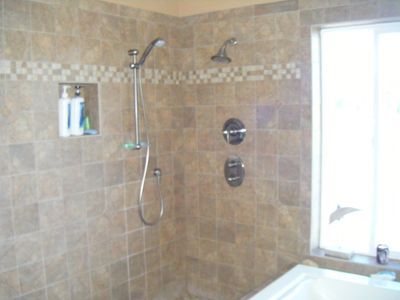 Open, two shower heads. walk in shower stall in master suite with view to water.