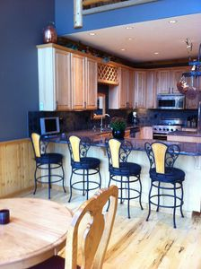 View of kitchen with barstools.
