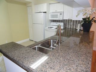 Sunny Isle condo photo - Spacious kitchen with granite countertops and stone backsplash