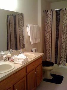 Guest bathroom w/ his & hers sinks, washer & dryer