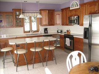 Lake Leelanau house photo - Large kitchen area with island and bar stools