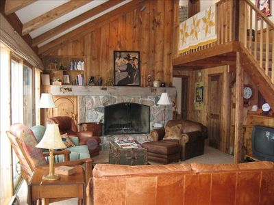 Living room: fieldstone fireplace, picture windows, seating for 8-9;