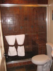 Upgraded bathroom has slate flooring, large tiled shower and ceiling heater
