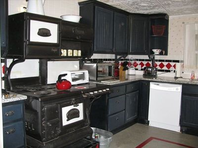 Kitchen features antique stove and modern appliances side-by-side.