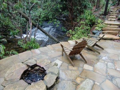 Relax along the banks of a cascading waterfall on your own stone patio w/fire