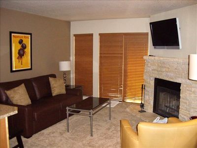 "39"" Flat Screen TV sits over a hand-hewn stone fireplace in the Living Room."