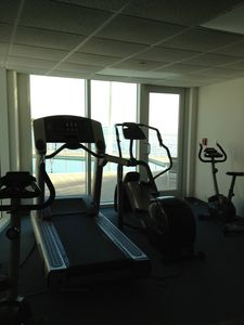 Gym next to the pool. Exercise looking at the water