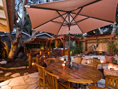 Patio table seating for six under a shade umbrella.