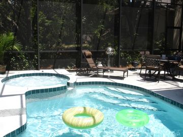 Heated pool and spa area with patio table and chaise