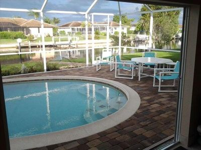 Beautiful heated pool with lanai and patio overlooking boat dock and canal