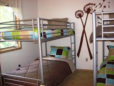 Twin bunk beds sleep four on upper level with shared full bathroom.