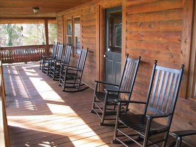Large wrap around shaded porch with rockers and swing overlooking water