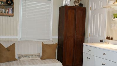 Pull out bed and cabinet with dishes, microwave and serving pieces.