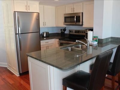 Renovated kitchen with stainless steel appliances, granite and new cabinets.