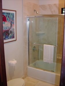 Thick Glass Shower enclosure over Tub . Premium travertine walls and flooring.