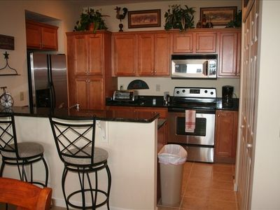 The fully equipped stainless steel kitchen boasts granite countertops.