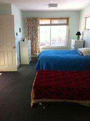 Rye house photo - Big bedroom with twin bed and 3/4 bed. This room also has a slider to back deck