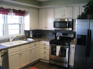 Kitchen, all stainless steel. Gas stove, large Island with chairs.