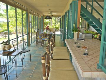 A large screened porch with dinning table