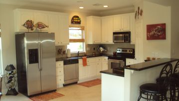 Kitchen with stainless steel appliances, granite countertops and barstools